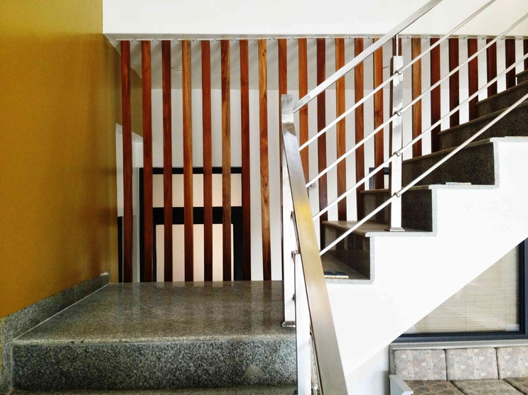 Steel railings on one side of the staircase and wood partitions on the other