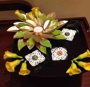 Gold metallic leaves, rice rangoli, flowers and diyas make up this Diwali decor.