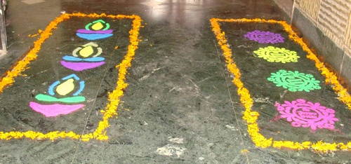 Diyas and rangoli patterns with colours and marigold petals
