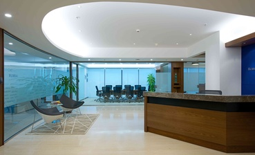 The free flowing form of the ceiling compliments the curved glass partitions in the reception area.