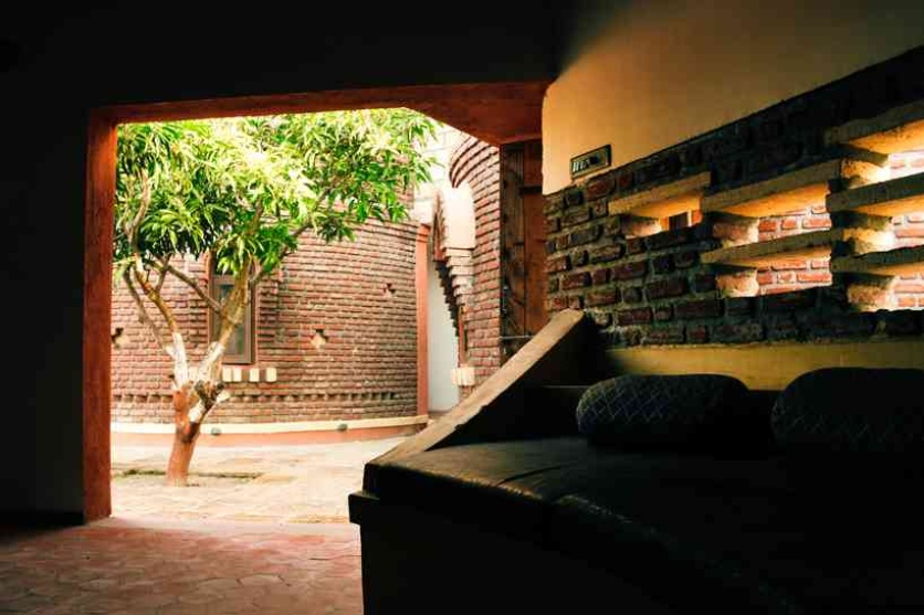 Courtyard with a mango tree within cottage cluster acts as a transition space between the more private cottage bedroom and the informal semi open living area