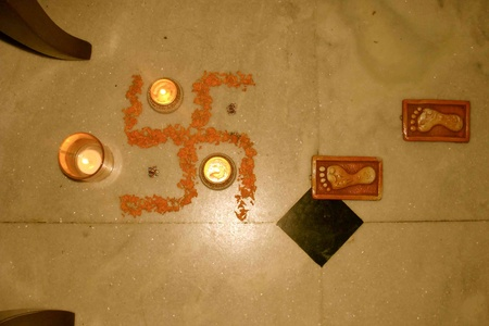 Swastik in marigold, diyas and Laxmi ji's footprints in terracotta
