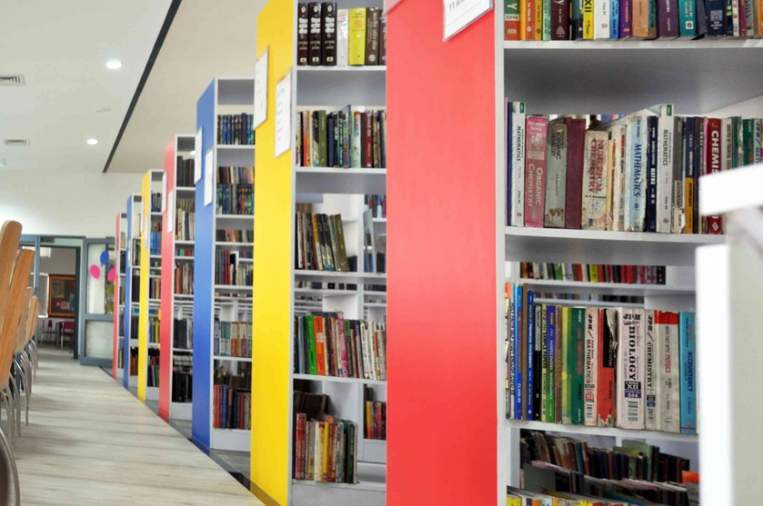 Vibrant yellow, red, blue book shelves pep it up for the readers