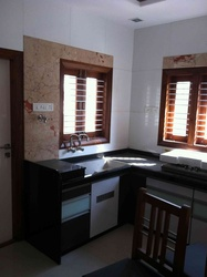 Open kitchen with white tiles and brown marble