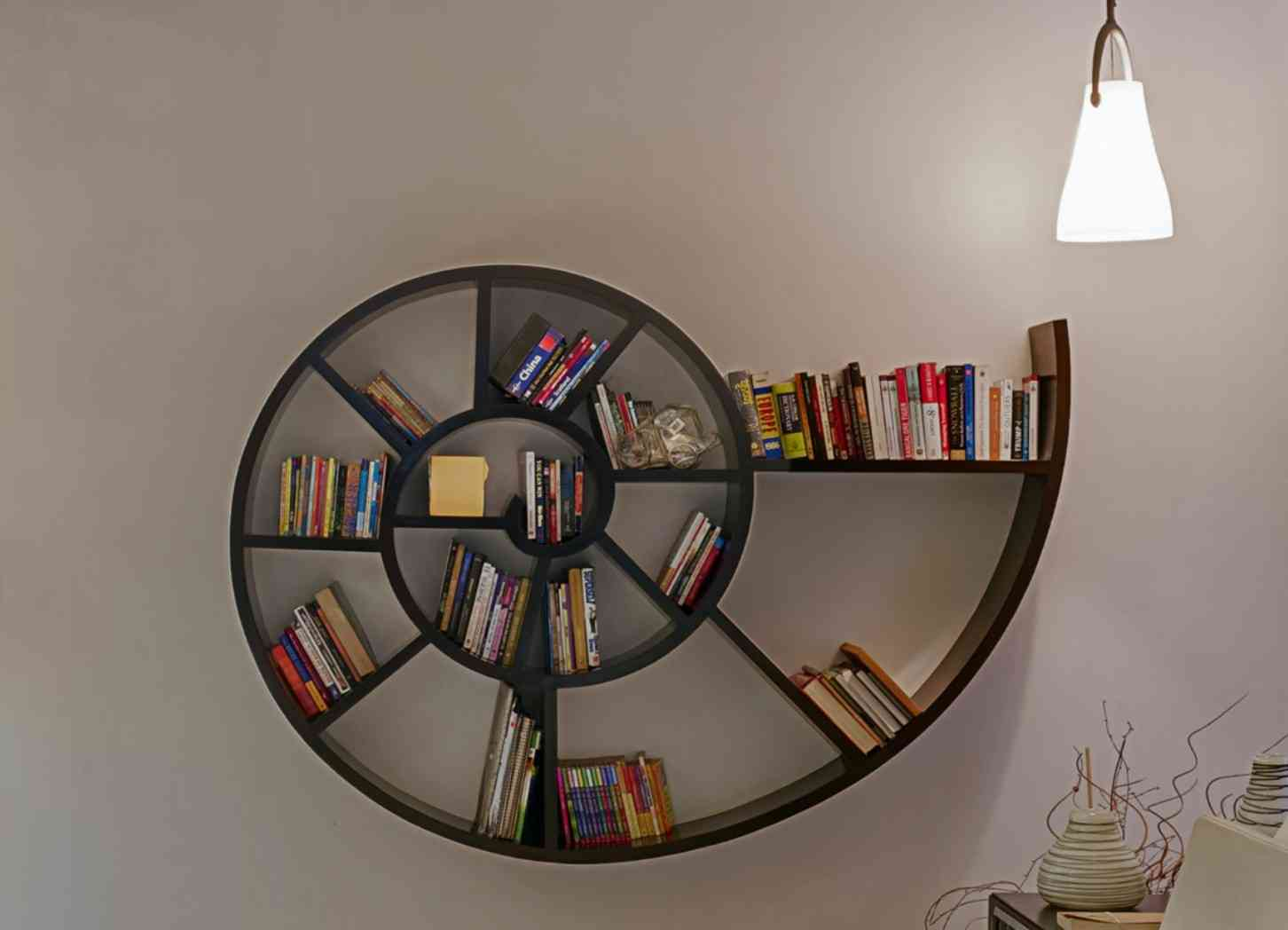 A spiral book rack allows numerous arrangement patterns while complementing the curving geometry of the cocoon-like bed