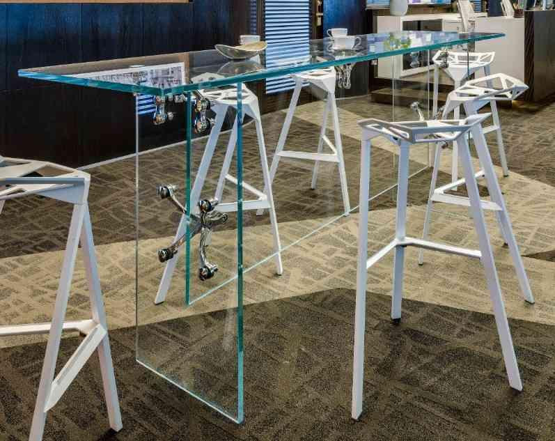 A see-through frameless glass table, accentuating its spider patches, brings out the jagged geometry of the bar chairs in this seating space