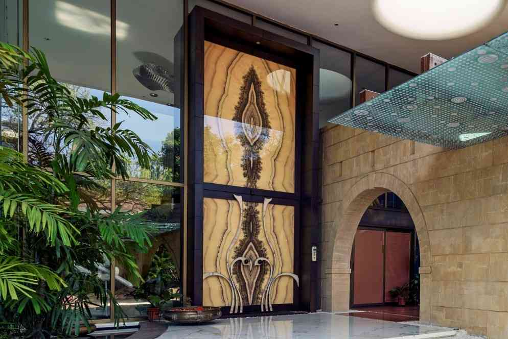 A grand onyx door marks a formal entry into the main foyer of a residence